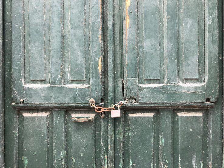 squatters in spain green door with padlock